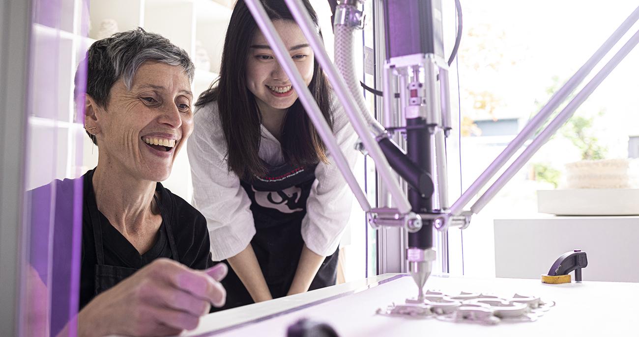 Timea Tihanyi and Wanna Huang at a 3D printer, watching a clay artwork develop.