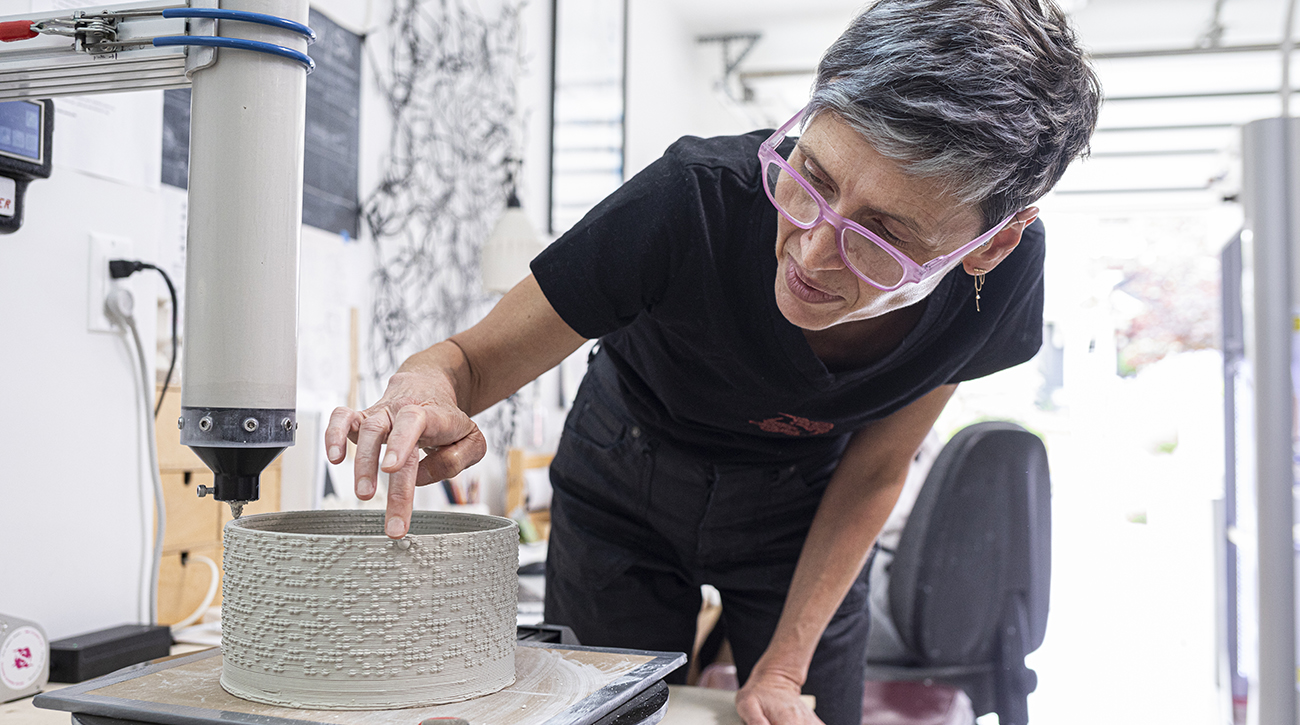Timea Tihanyi watching over an artwork being built using a 3D printer.