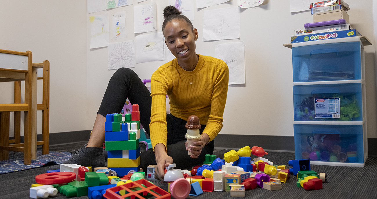 Deja Edwards on the floor with toys in the Social Cognitive Development Lab.