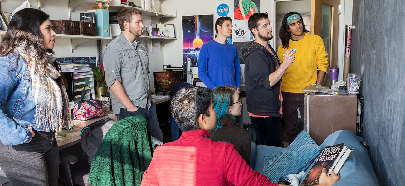 Seven astrobiology graduate students gather around a blackboard to discuss their work.