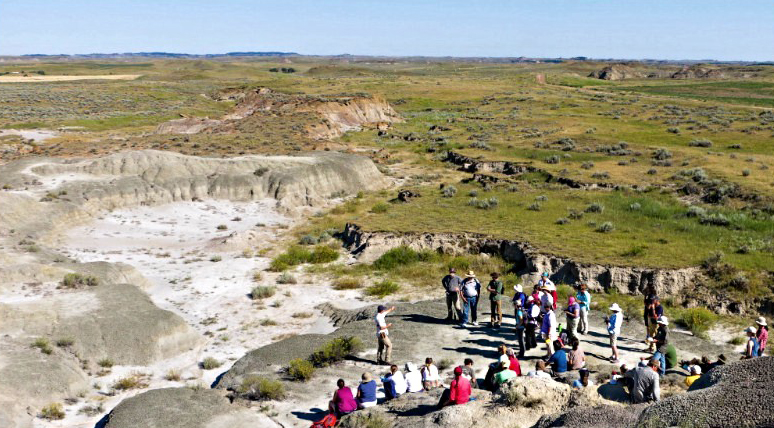 The group gathers as Greg WIlson provides background about the geologic history of the vast Montana site.