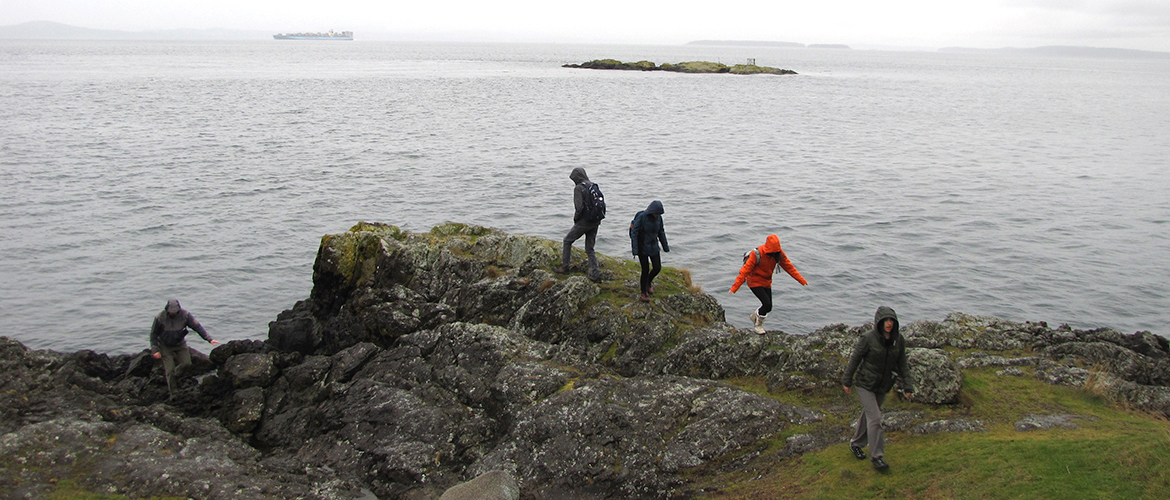 Students climbing a rocky outcrop with the sea beyond, on a grey day.