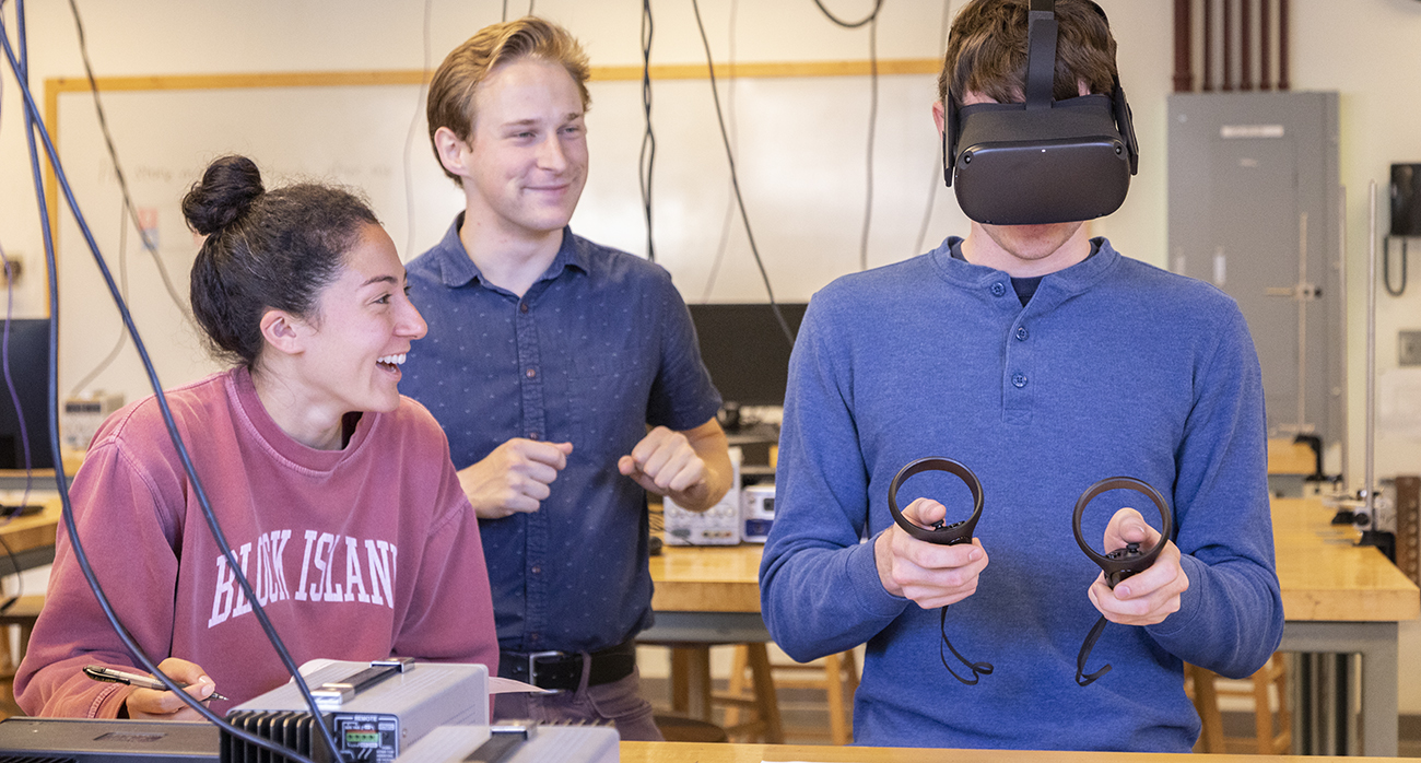 While a student wears an immersive headset to try an experiment, Jared Canright and another student look on.