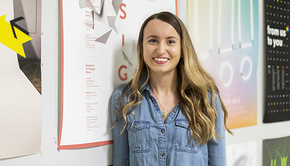 Interaction design major Sarah Stricker poses in front of design posters in UW's Art Building.