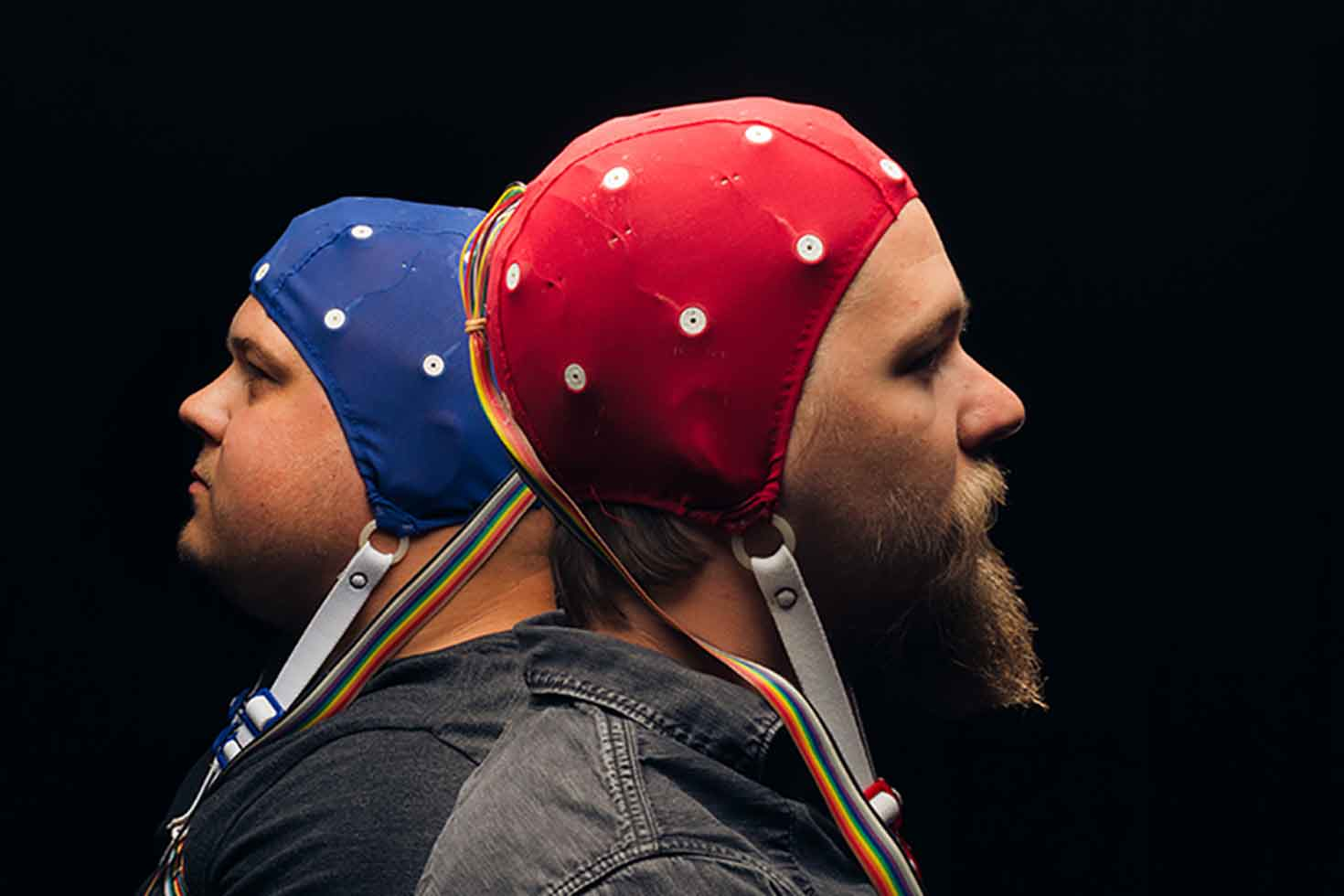 DXArts Project featuring two men wearing EEG caps to monitor neural oscillations