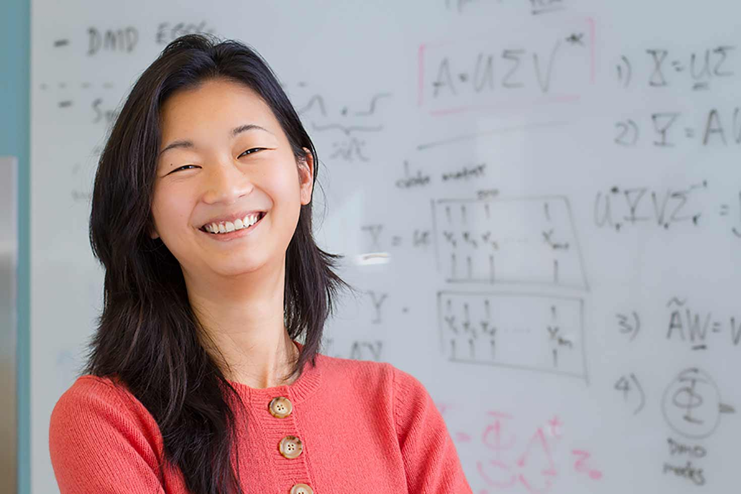Faculty member standing in front of white board covered in equations and diagrams