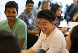 Students sitting at a table and laughing